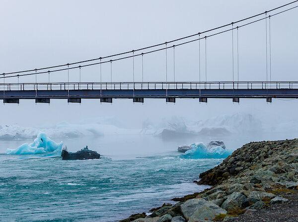 Eisberge treiben langsam unter der Brücke hindruch ins Meer