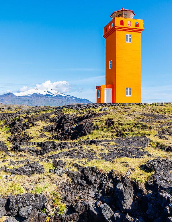 Der orangefarbene Svörtuloft Leuchtturm mit dem Snæfellsjökull in Hintergrund